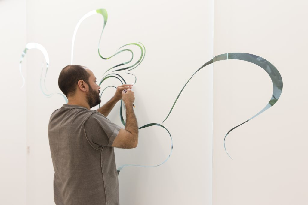 Pedro Varela working on the kaleidoscopic swirls in his large adhesive vinyl installation at Zipper Galeria
