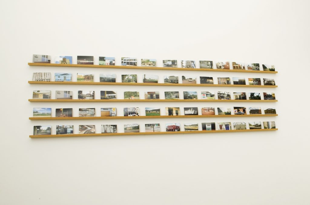 Rivane Neuenschwander, Mapa Mundi BR (Postal), 2007, Postcards and wood shelves/Photo: Eduardo Ortega