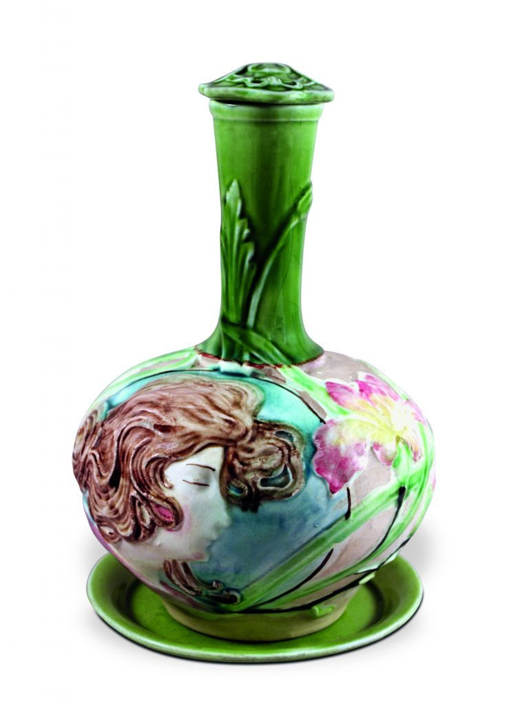 Eliseu Visconti-designed green ceramic vase with woman's face carved into side.