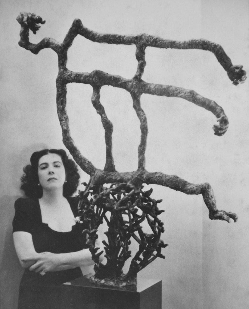 Maria Martins poses next to sculpture with arms crossed