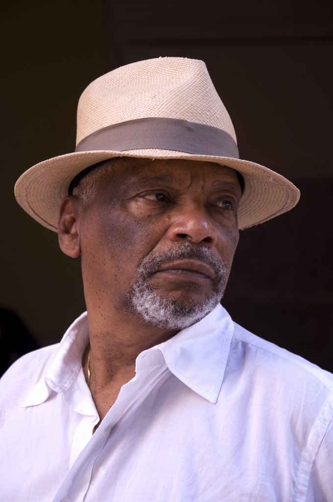 Artist Emanoel Araujo wearing a hat and white shirt