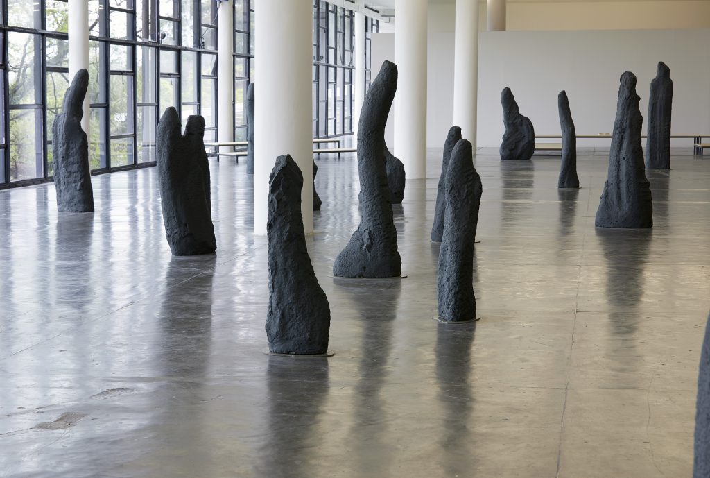 Tall black sculpture forms scattered around an open gallery space