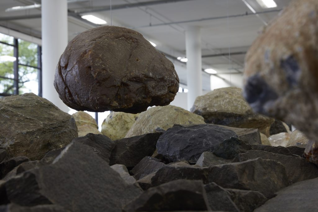 Exhibition room showing large rocks in formation, including a couple hanging above from wires.