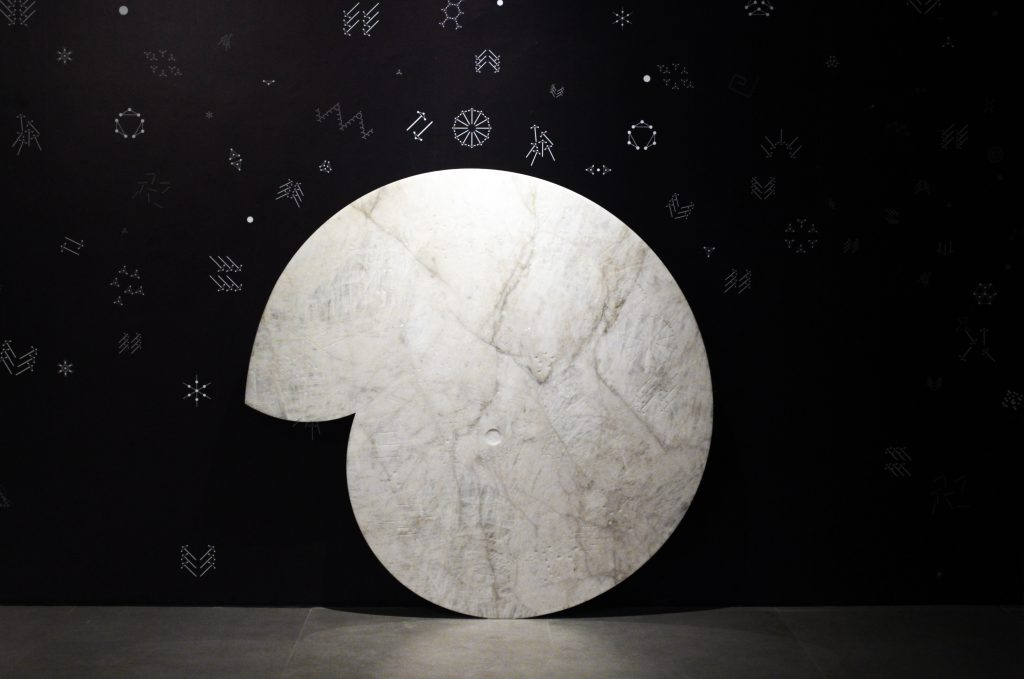 Denise Milan sculpture of circular quartz with symbols on wall around it
