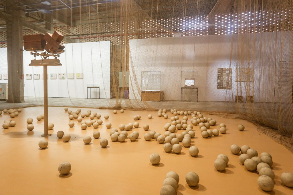 Cildo Meireles sculpture showing netted court with wooden balls placed all around the floor.
