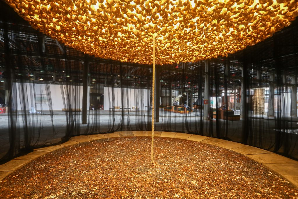 Cildo Meireles sculpture showing six hundred thousand coins on floor attached to two thousand bones above via narrow string of eight hundred communion wafers.