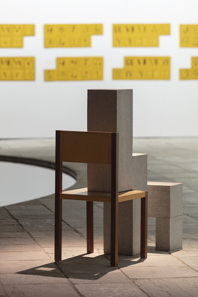 Cildo Meireles sculpture showing wooden chair with concrete blocks stacked on top of seat.