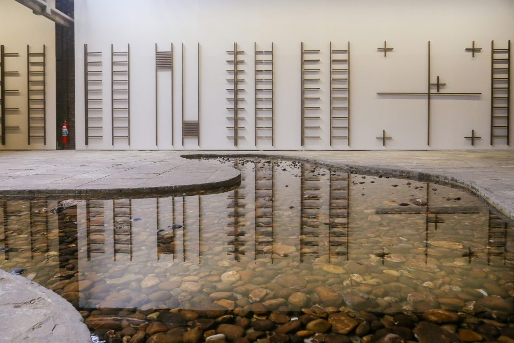 Two Cildo Meireles sculptures: one showing irregular shaped pond with rocks at bottom; the other showing a series of ladders with missing pieces.